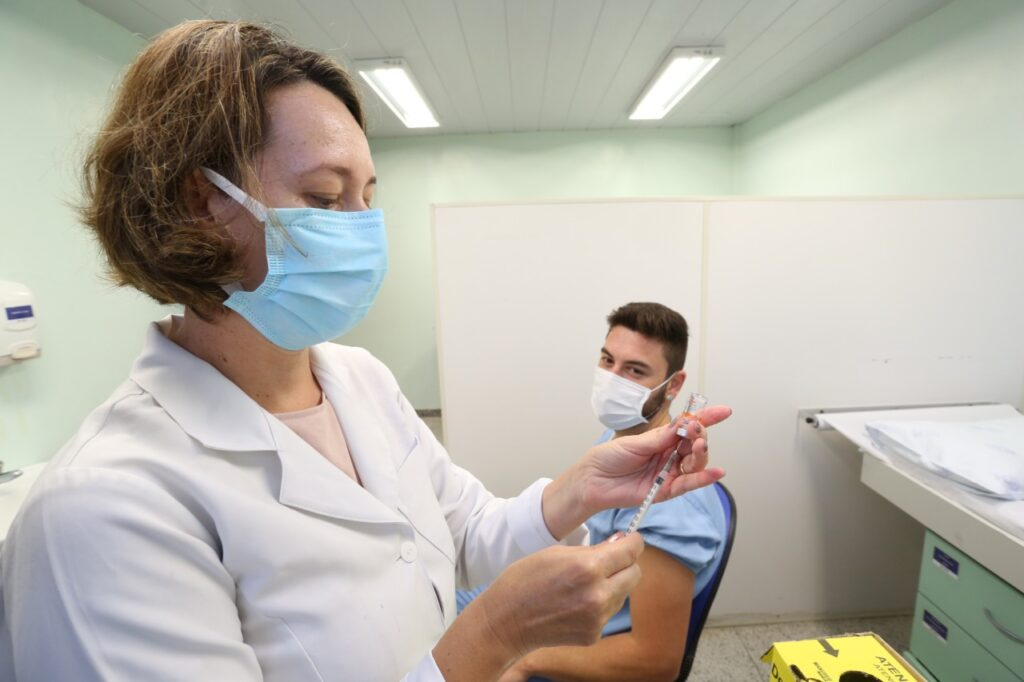 Profissional da saúde prepara vacina para ser aplicada e é observada por paciente